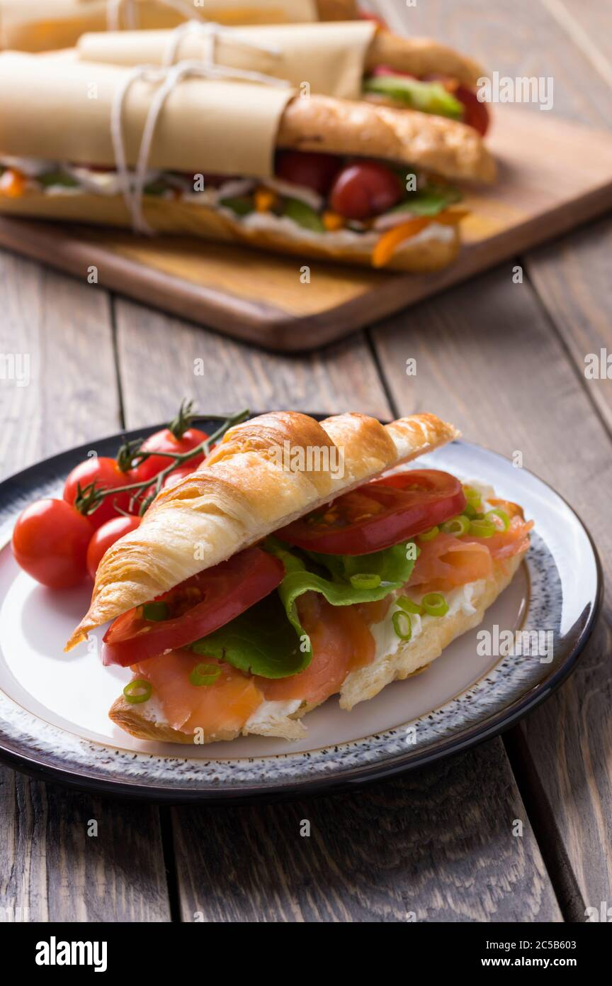 Fresh submarine sandwiches with varieties of fillings on wooden background Stock Photo