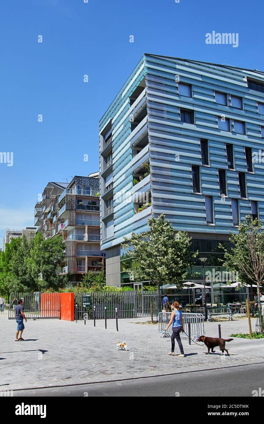 Paris, France - June 28, 2015: Eco-Quartier Clichy-Batignolles. New Modern Architecture. Park Martin Luther King. The girl is walking the dogs Stock Photo