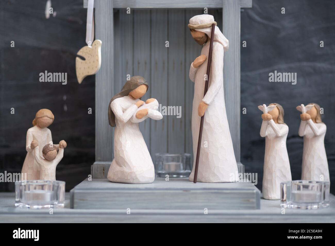Wooden figurines depict a Christmas nativity scene in a simple wooden stable. Stock Photo