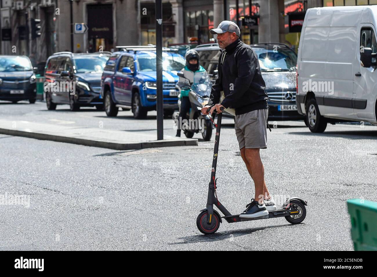 London, UK.  2 July 2020. A man rides a personal electric scooter (e-scooter) in Regent Street.  The Department of Transport will allow rental e-scooters to become legal on roads in Great Britain from 4 July, for a 12 month trial period, to try to ease pressure on public transport during the coronavirus pandemic.  Riders need a full or provisional car, motorcycle or moped licence to use the vehicles, and they must be aged 16 or over.   Currently, it is an offence to ride personal e-scooters on a UK public road, cycle lane or pavement. Credit: Stephen Chung / Alamy Live News Stock Photo