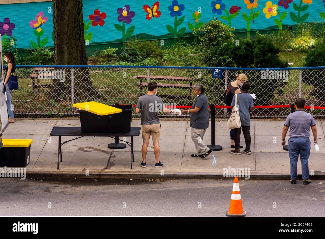 People in need line up for clothing and food at the Relief Bus social services in the Chelsea neighborhood of New York on Wednesday, July 1, 2020. (© Richard B. Levine) Stock Photo