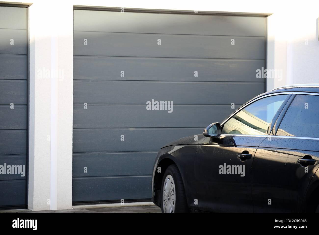Modernes neues Garagentor (Sektionaltor) mit davor parkendem Auto Stock Photo