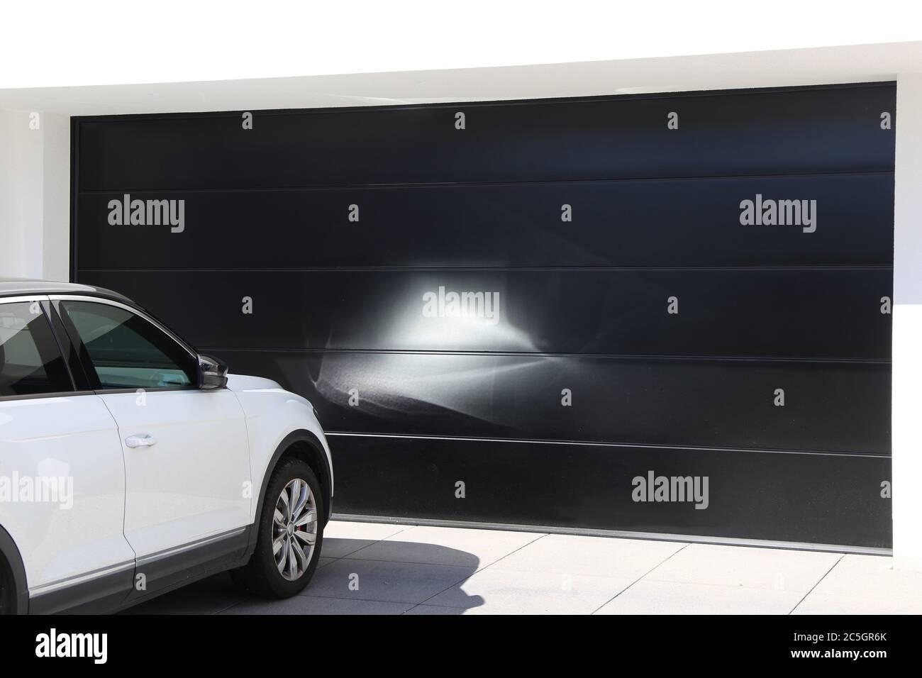 Modernes schwarzes Garagentor (Sektionaltor) mit davor parkendem weißen PKW Stock Photo