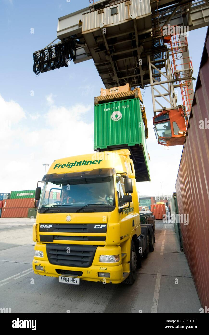 Rail mounted crane being used to load and unload shipping containers on HGV lorries at Manchester Euroterminal, Trafford Park, Manchester, England. Stock Photo