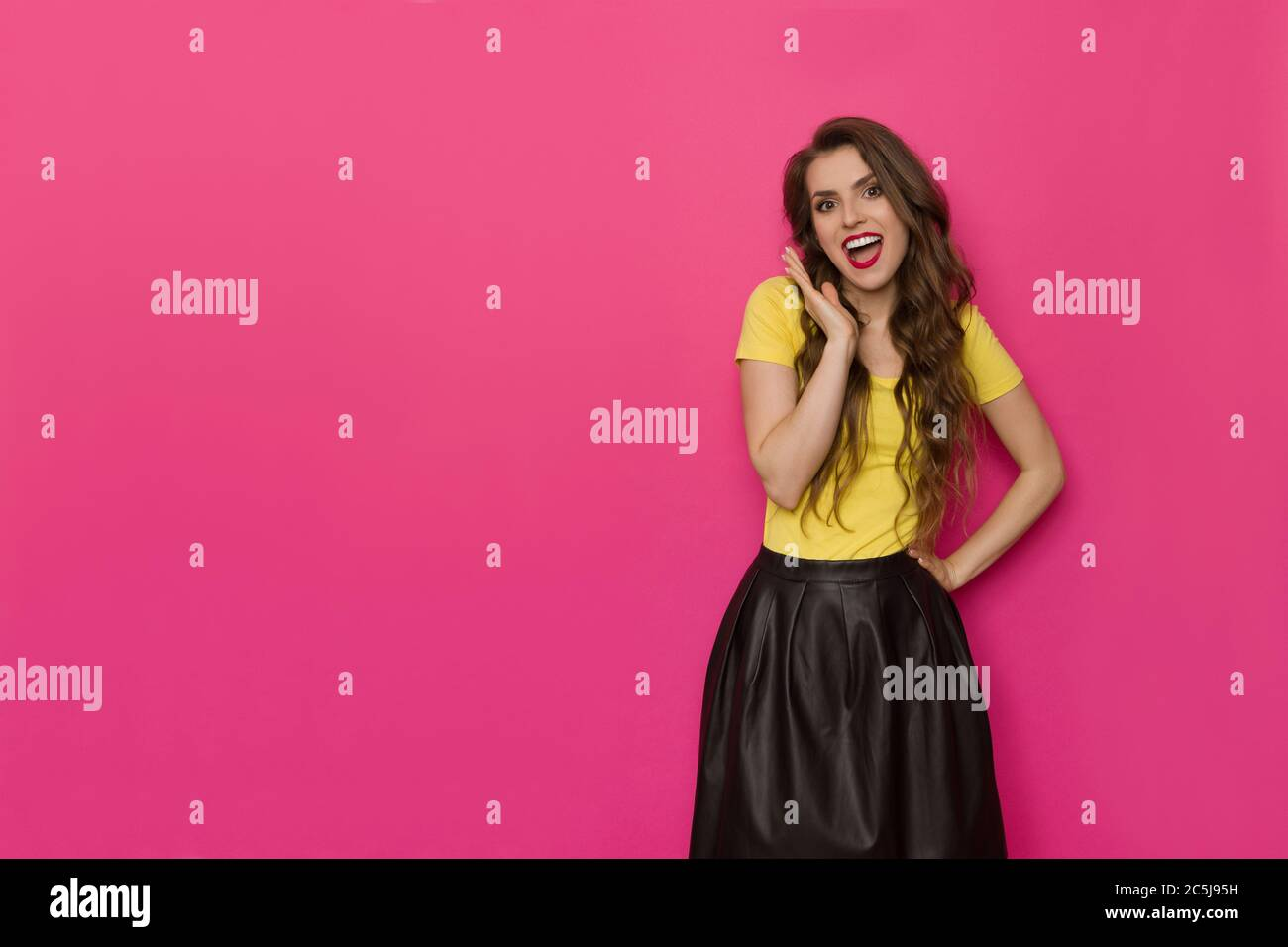 Excited beautiful woman in yellow top and black skirt is holding hand on chin, looking at camera and shouting. Three quarter length studio shot on pin Stock Photo