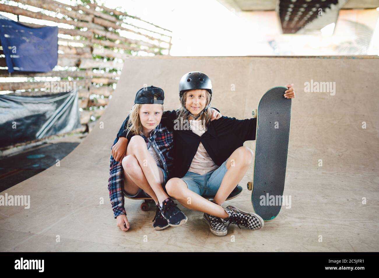 Group of children friends enjoying day at skate park. Youth, togetherness and friendship concept. Group of kids skateboarders. Urban little ones Stock Photo