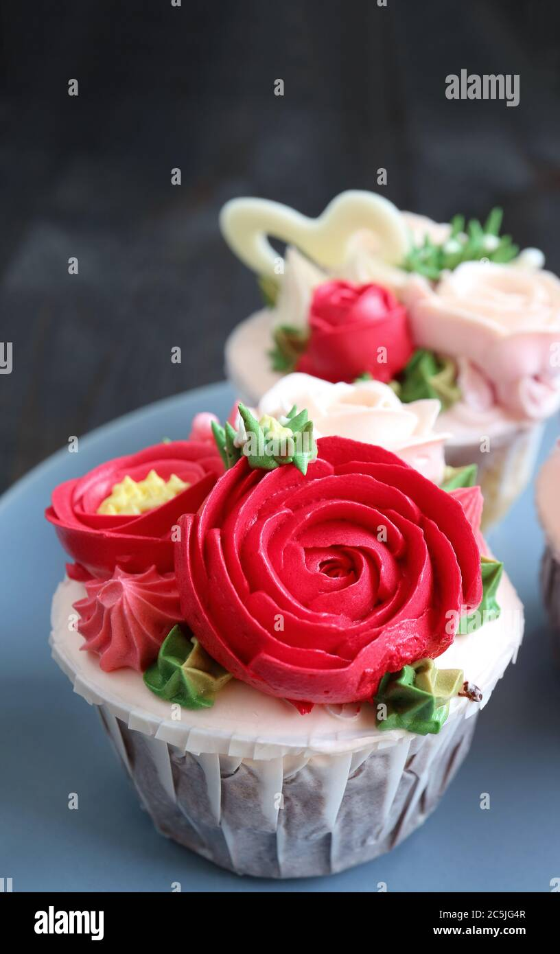 Closeup Cupcakes Decorated With Red Flower Shaped Frosting On Pale Blue Plate Stock Photo Alamy