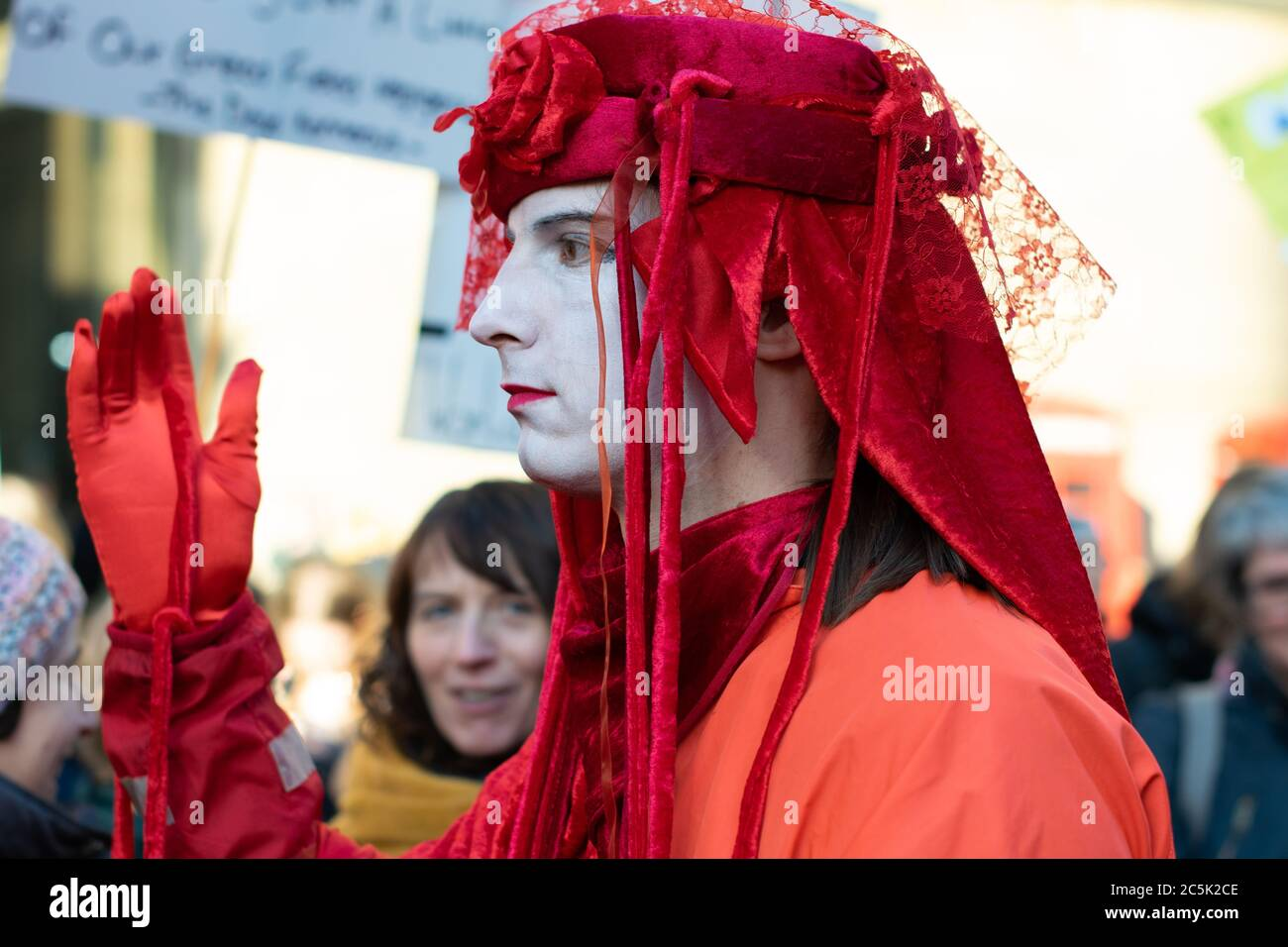 Global climate strike in St Peter's Square, Manchester UK. Extinction rebellion invisible circus red rebels. Man in profile with hand held up Stock Photo