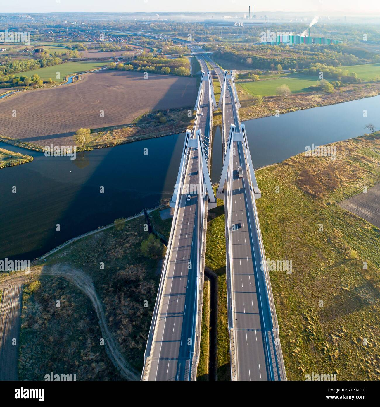 New modern double cable-stayed bridge with wide three-lane roads over Vistula River in Krakow, Poland. Part of the ring road around Krakow. Aerial vie Stock Photo