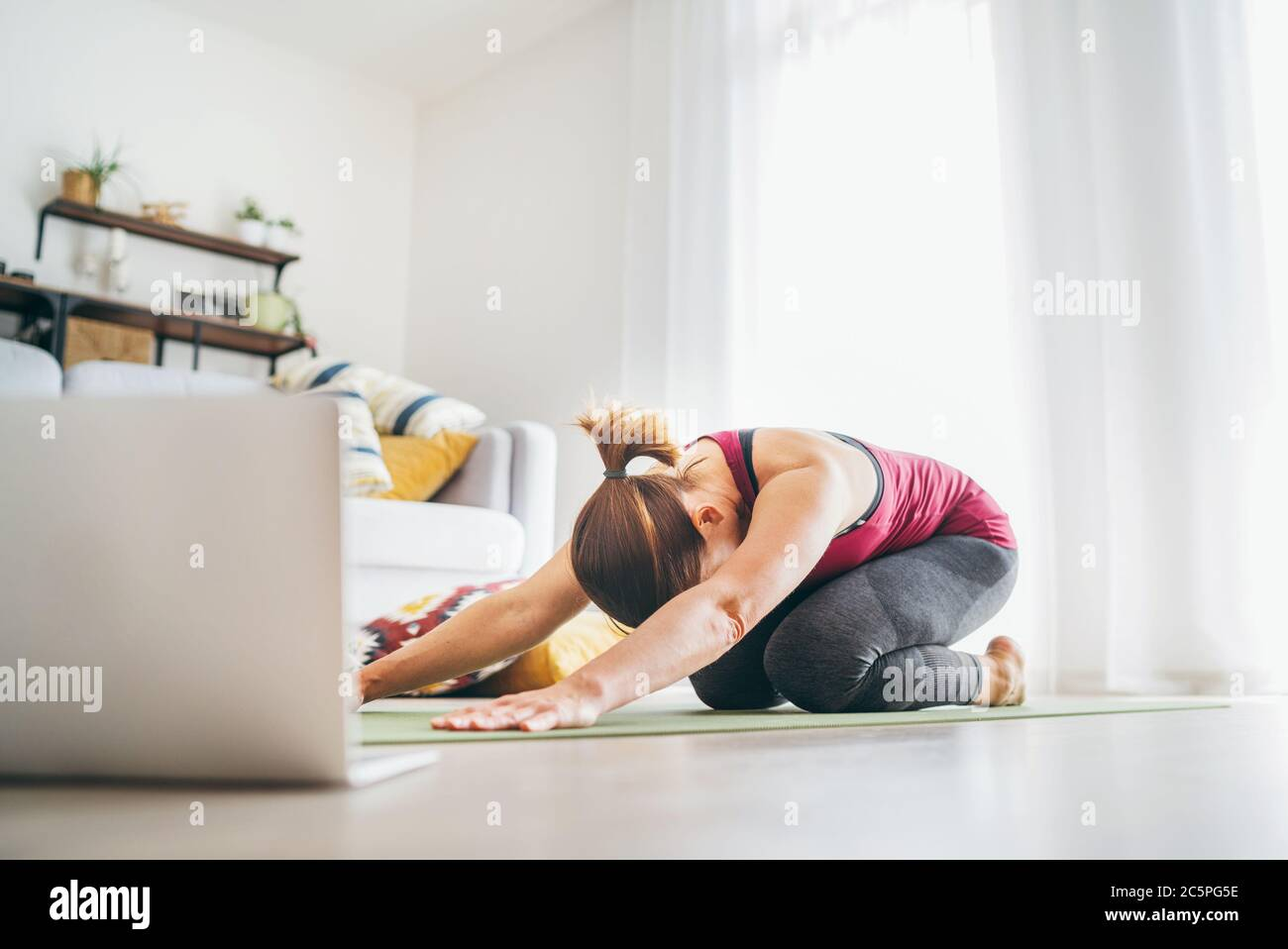 Fit sporty healthy woman on mat in Child's Balasana gentle resting yoga pose, doing breathing exercises, watching online yoga class on laptop computer Stock Photo