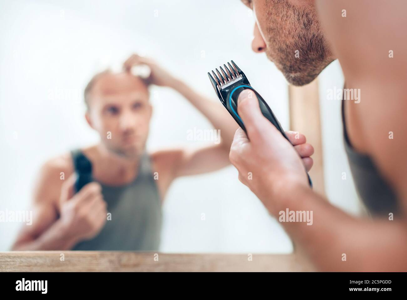 Man looking at bathroom mirror and thinking about his new style haircut analyzing hairs.Electric rechargeable Trimmer close up focus image. Radical de Stock Photo