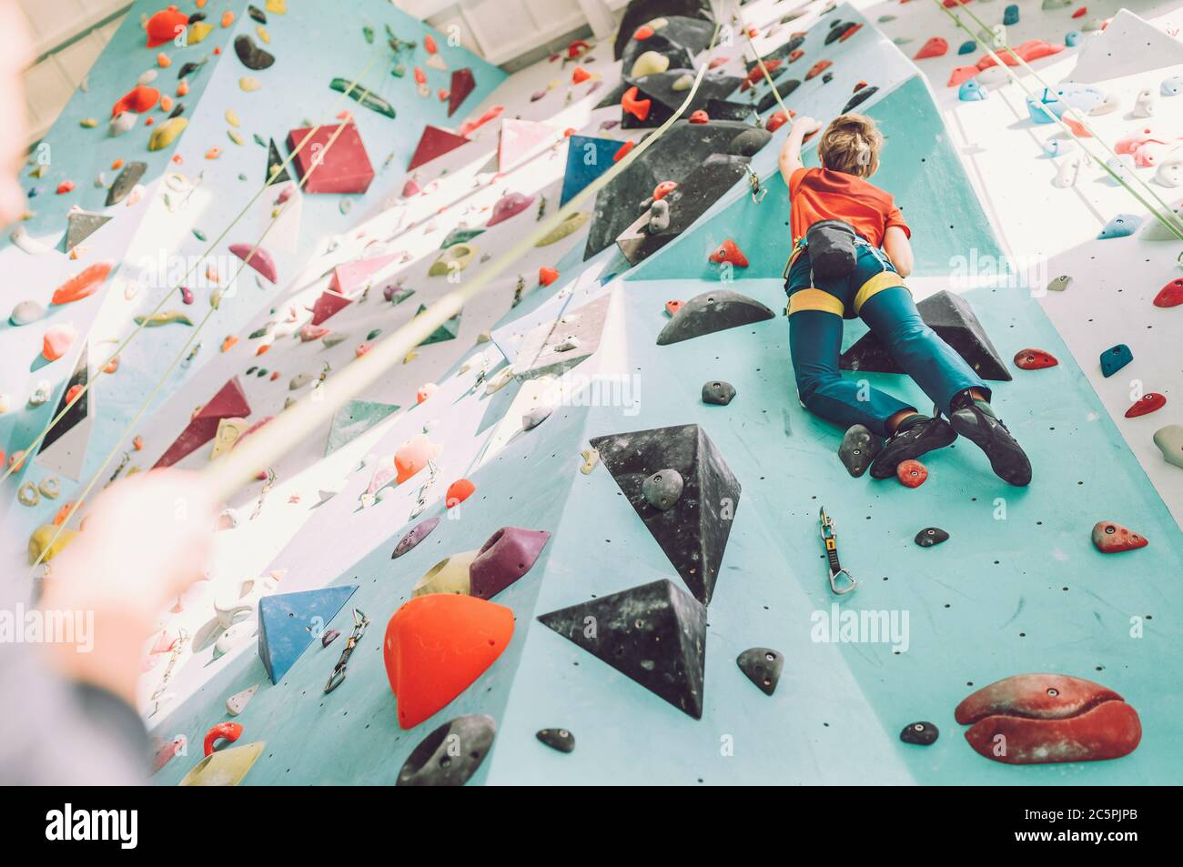 Teenager boy at indoor climbing wall hall. Boy is climbing using a top rope and climbing harness and somebody belaying him from floor. Active teenager Stock Photo