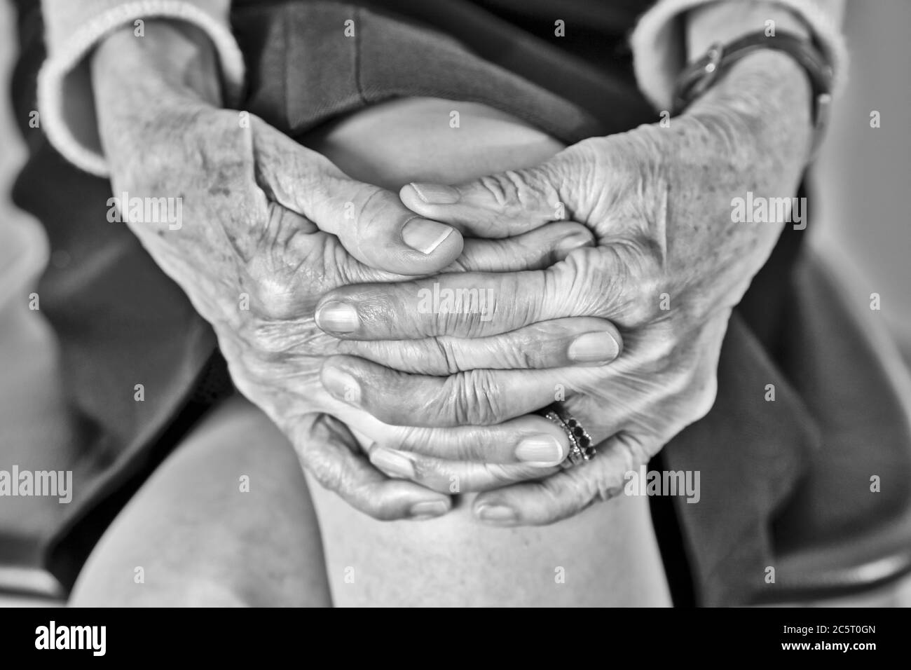 Elderly woman sitting with joined hands Stock Photo