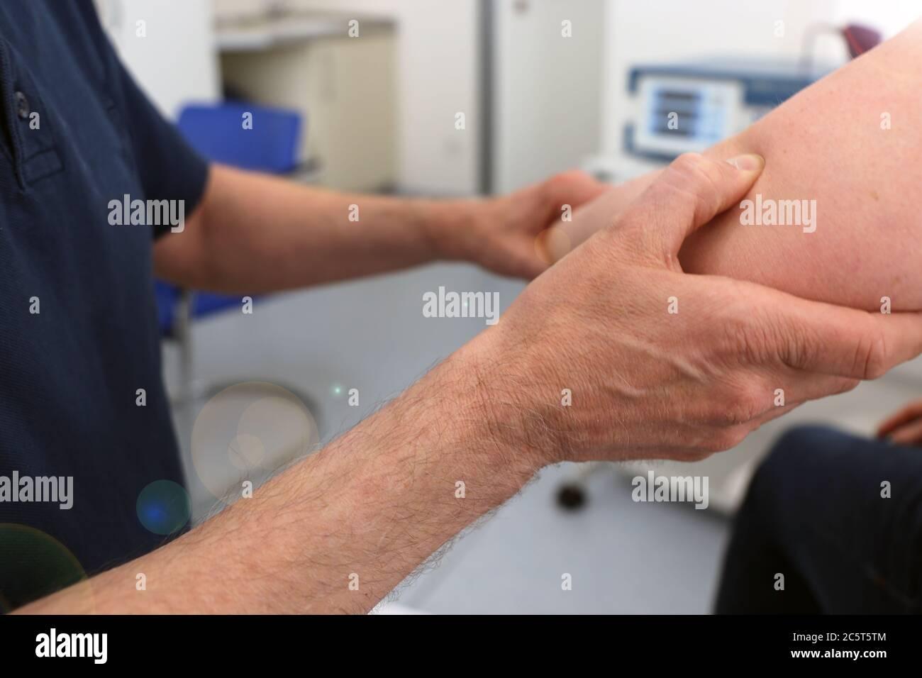 Orthopäde untersucht den Ellenbogen einer Patientin Stock Photo
