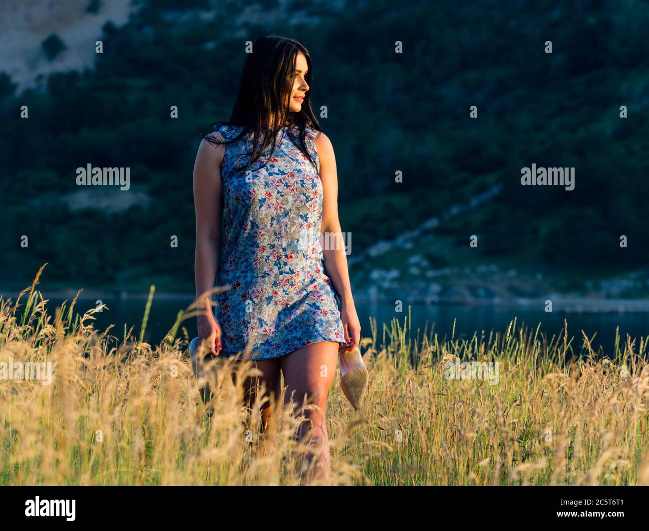 Teengirl going go returning home watching sunrise in distance walking barefeet on Summer grassfield tall grass holding high-heels shoes in hands Stock Photo