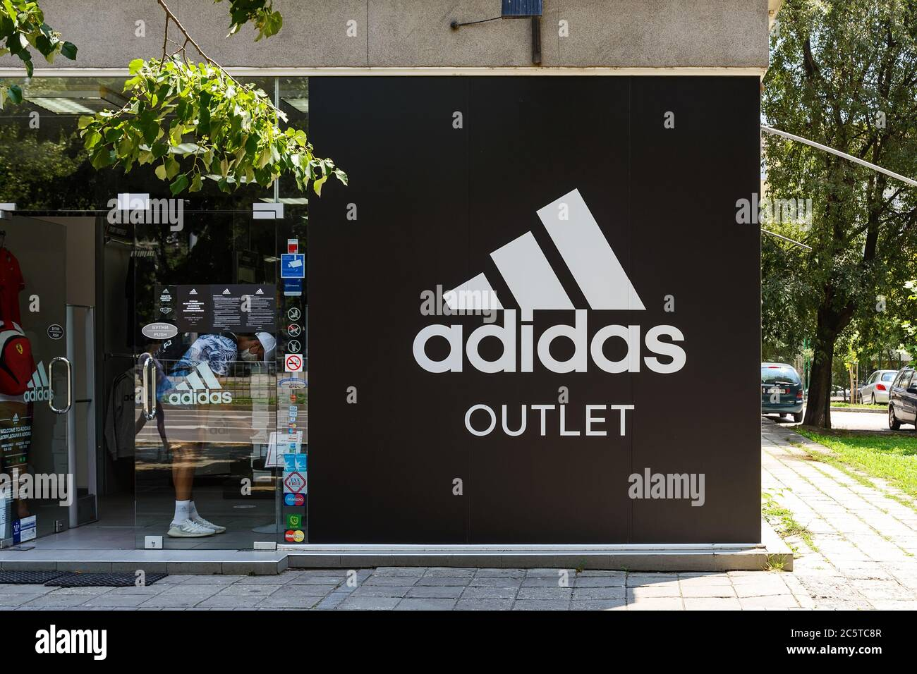 Diligencia Inyección Allí  Varna, Bulgaria, July 01, 2020. Entrance to Adidas outlet shop from a city  street on a sunny summer day. Signboard of Adidas logo brend sign on store  Stock Photo - Alamy