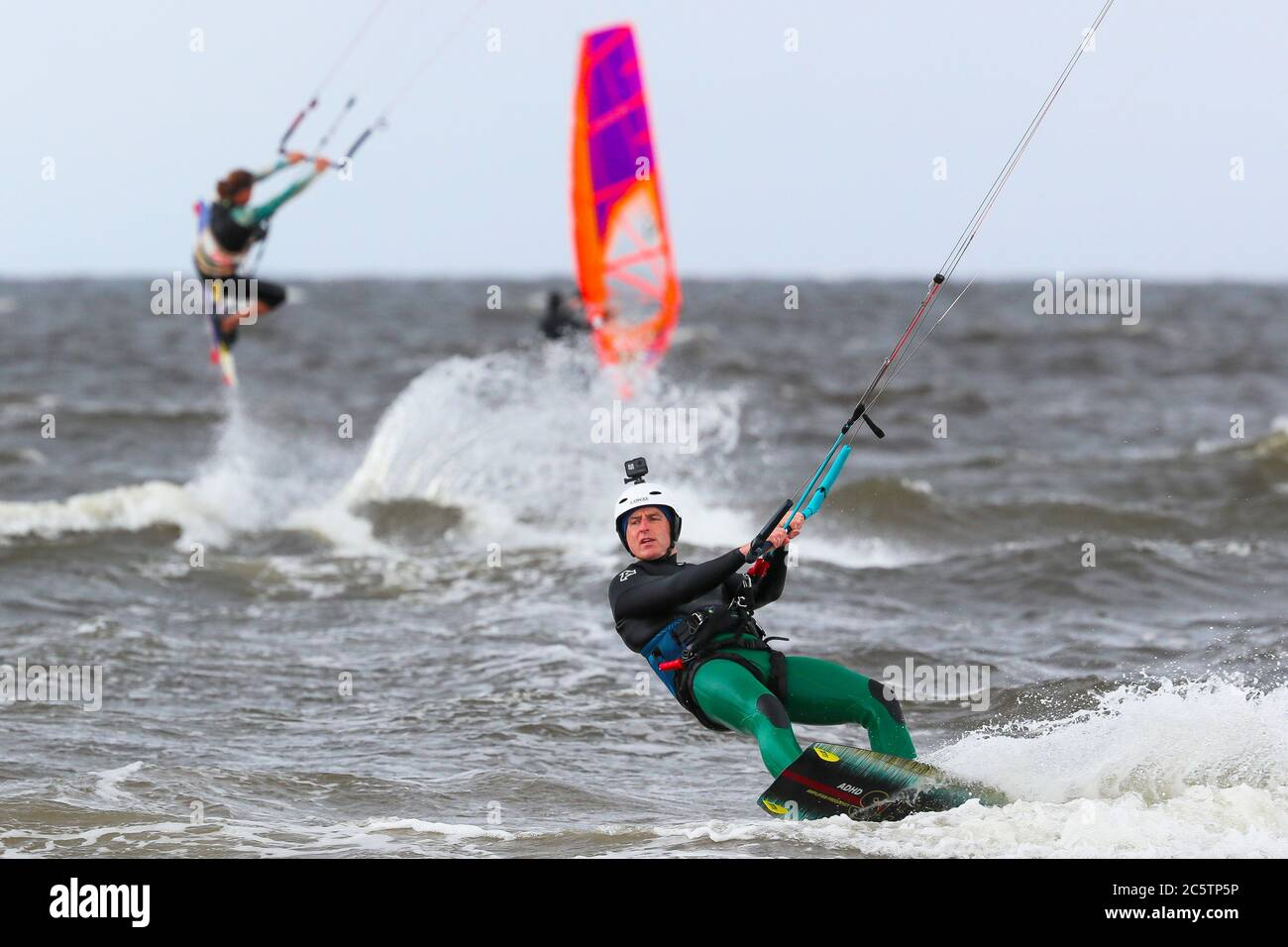 Troon, UK. 05th July, 2020. Gusty winds up to 50 mph attracted windsurfers to the beach at Troon to enjoy their hobby. on the Firth of Clyde. Credit: Findlay/Alamy Live News Stock Photo