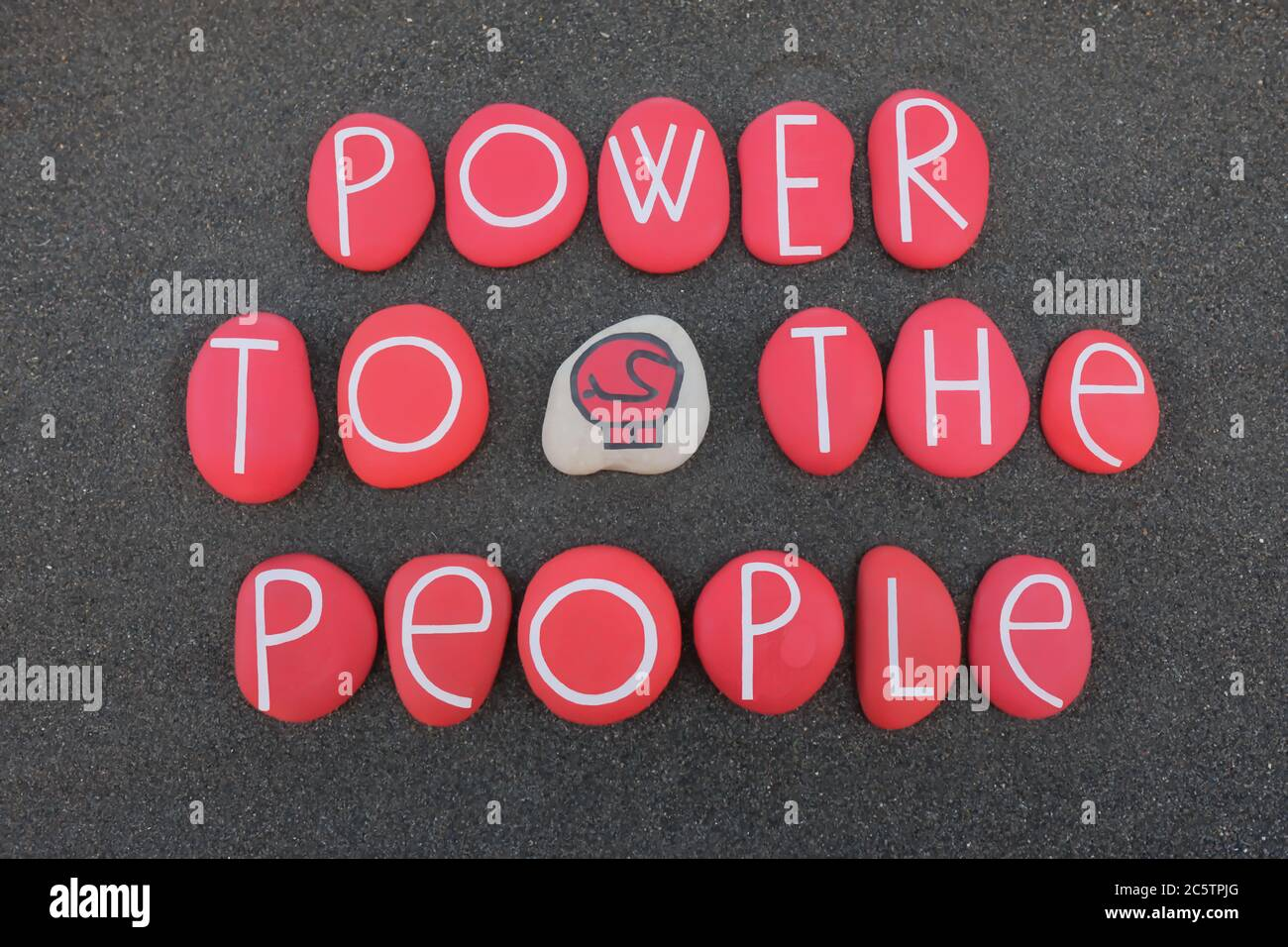 Power to the people, protest slogan composed with red colored stones over black volcanic sand Stock Photo
