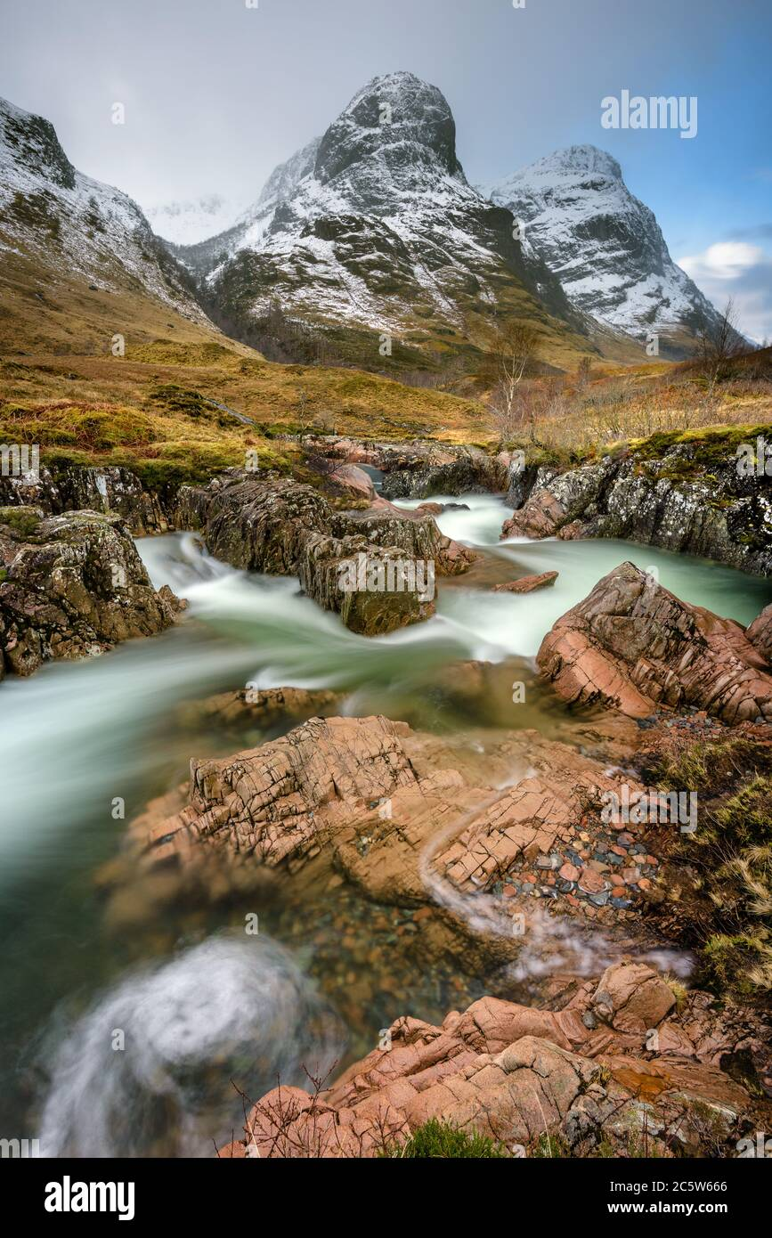 Three Sisters mountain range in Glencoe covered in layer of Winter snow with interesting rocky stream in foreground. Scottish Highlands, UK. Stock Photo