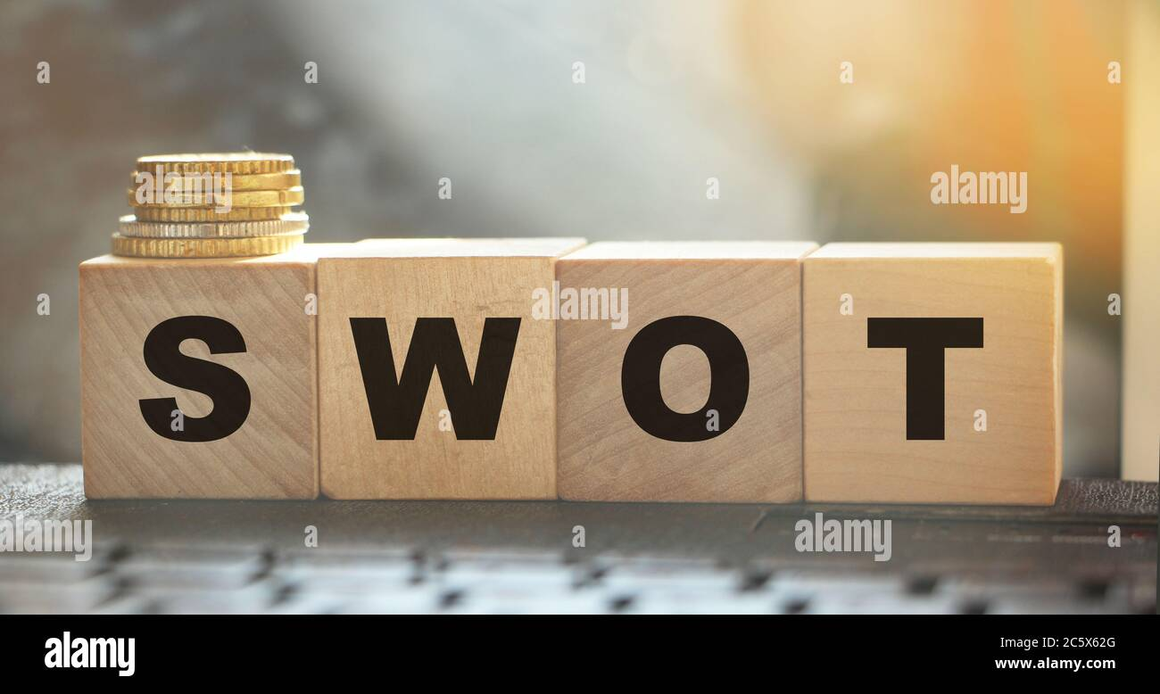 SWOT on wooden cubes and coins on computer keyboard. Business concept Stock Photo