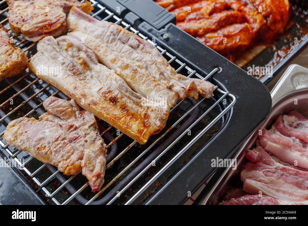 Top View Of Piece Of Barbecue Pork Belly And Grilled Steak On Electric Grill Griddle Surrounded With Raw Meat On Side Stock Photo Alamy