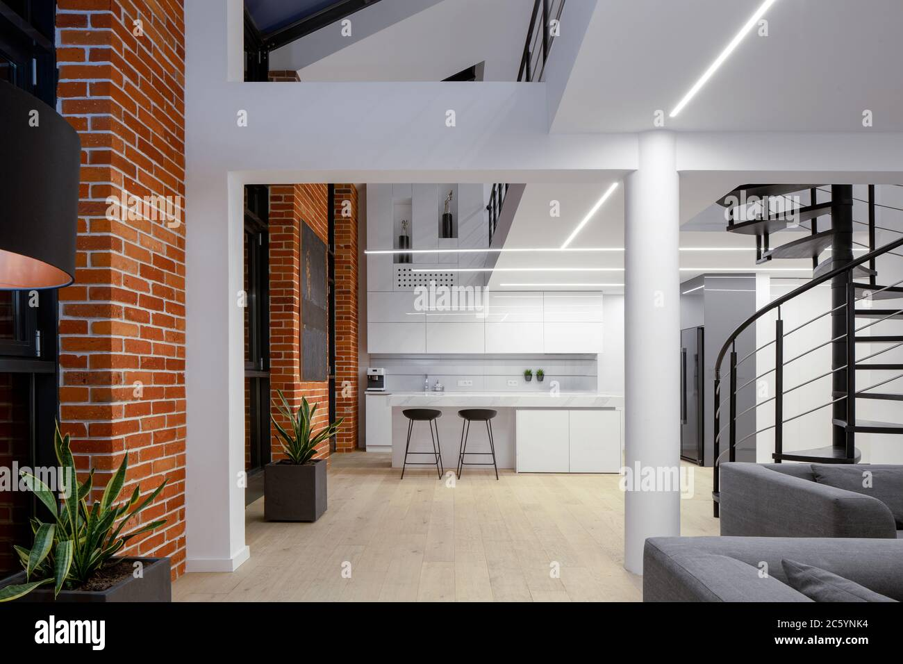 Spacious Two Floor Apartment With Brick Walls White Pillars And Wooden Floor Stock Photo Alamy