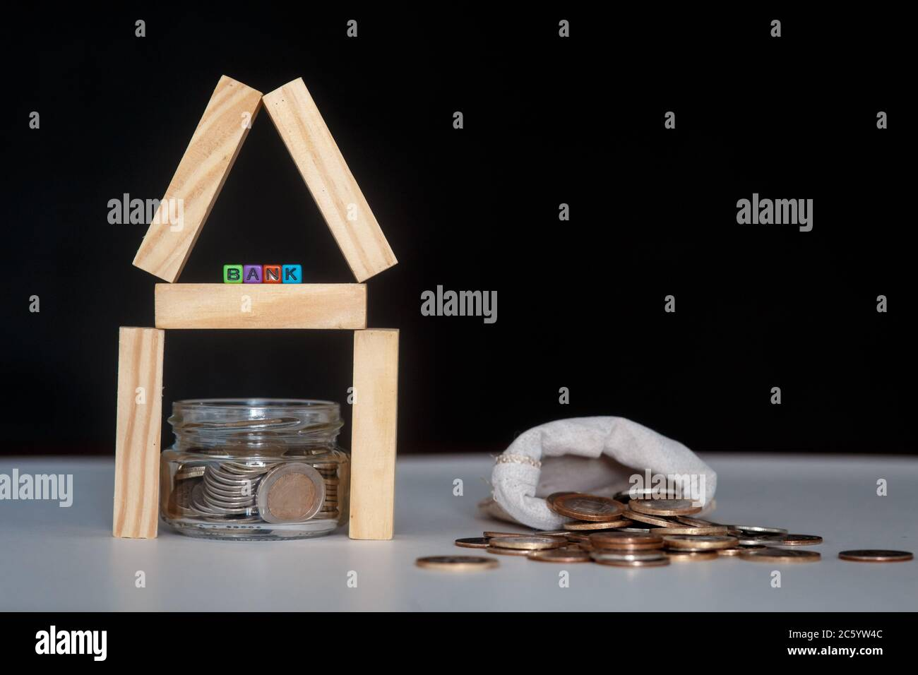 Glass bank with many world coins, house word or label on money jar and wooden home geometric blocks over table Stock Photo