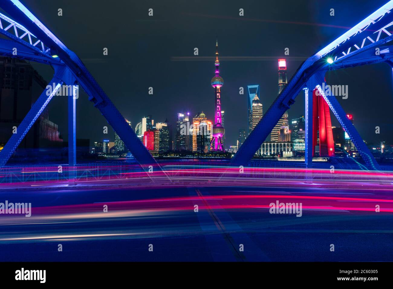 Night view of Waibaidu Bridge, a landmark steel bridge in Shanghai, with traffic and modern skyscrapers in the back. Stock Photo