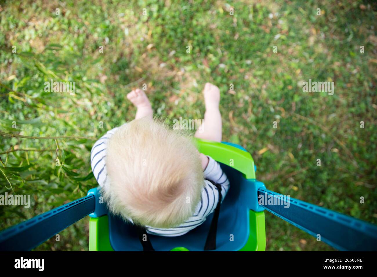 A little boy having fun playing on a swing under a tree in a garden Stock Photo