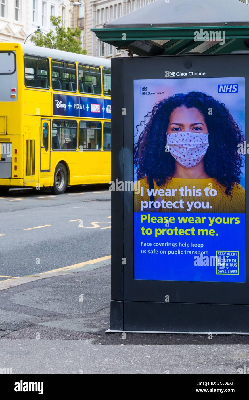 Face coverings help keep us safe on public transport stay alert control the virus save lives poster with Yellow bus behind at Bournemouth, Dorset UK Stock Photo