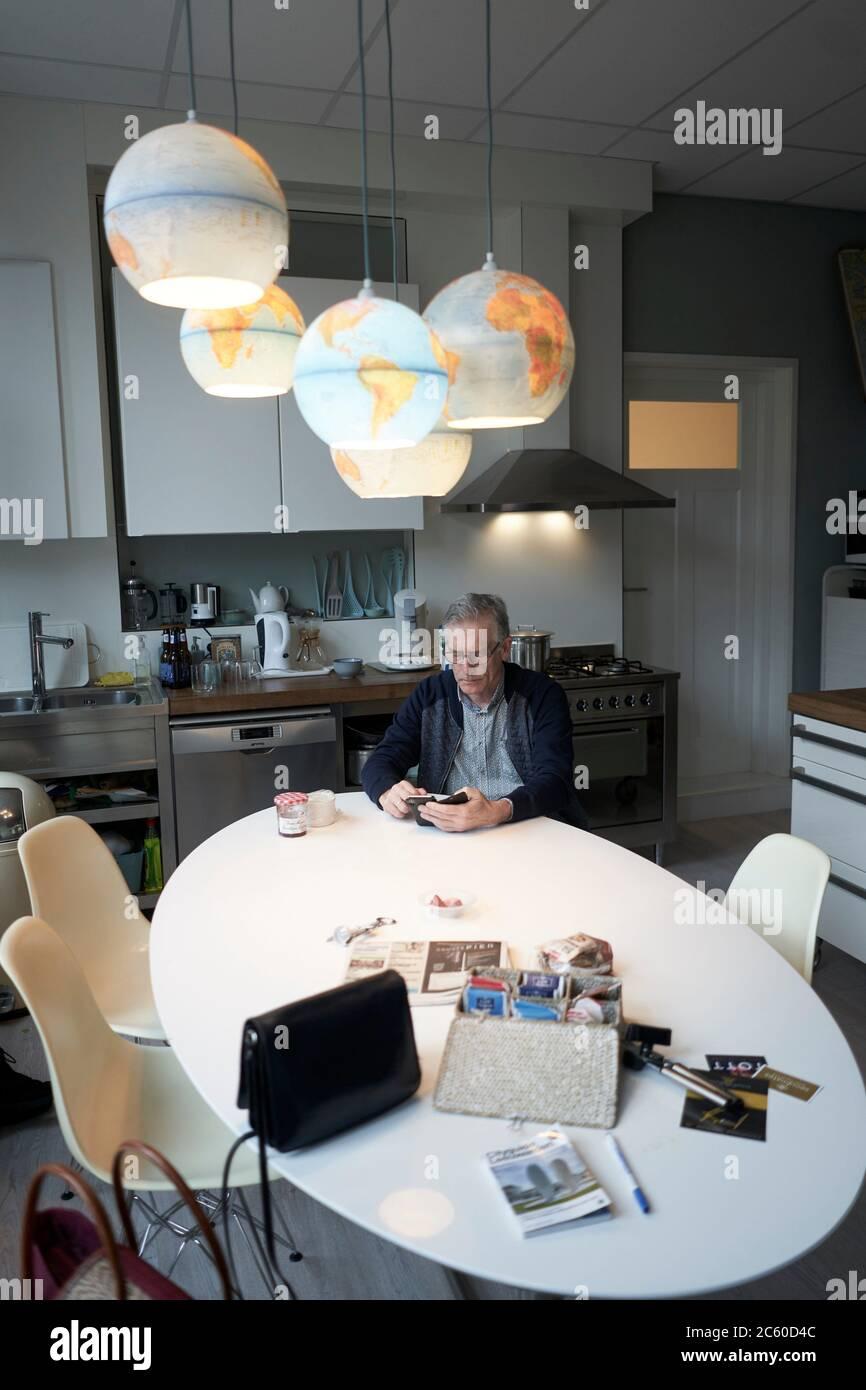 senior man using smartphone at breakfast table in kitchen. Stock Photo
