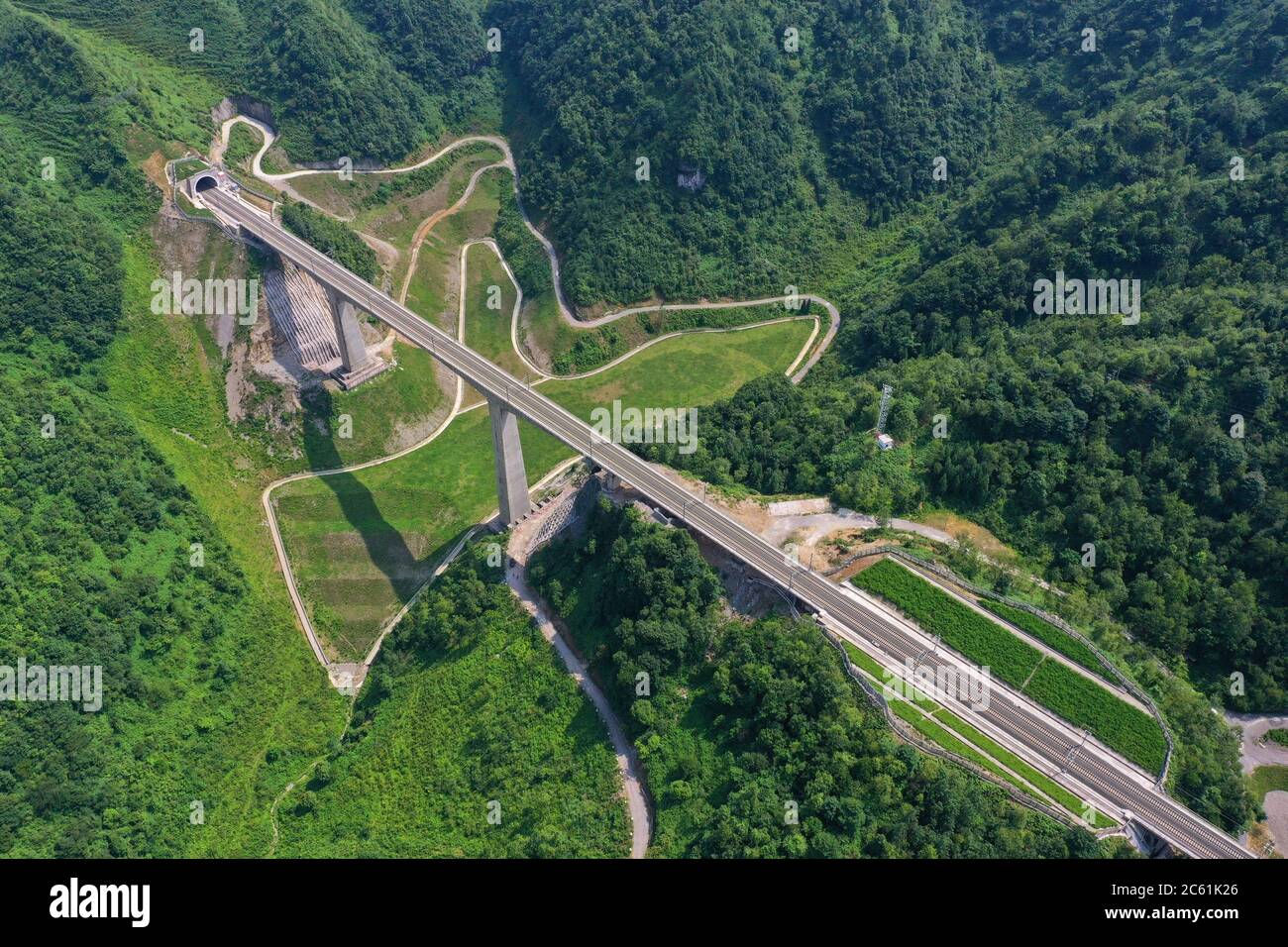 Liupanshui. 6th July, 2020. Aerial photo taken on July 6, 2020 shows a railway bridge along the Anshun-Liupanshui railway in southwest China's Guizhou Province. The Anshun-Liupanshui intercity railway, with a designed speed of 250 km per hour, is being prepared for opening. The railway will shorten the travel time between Guiyang and Liupanshui from the current 3.5 hours to about 1 hour, and Liupanshui City will be fully connected with the national high-speed rail network. Credit: Liu Xu/Xinhua/Alamy Live News Stock Photo