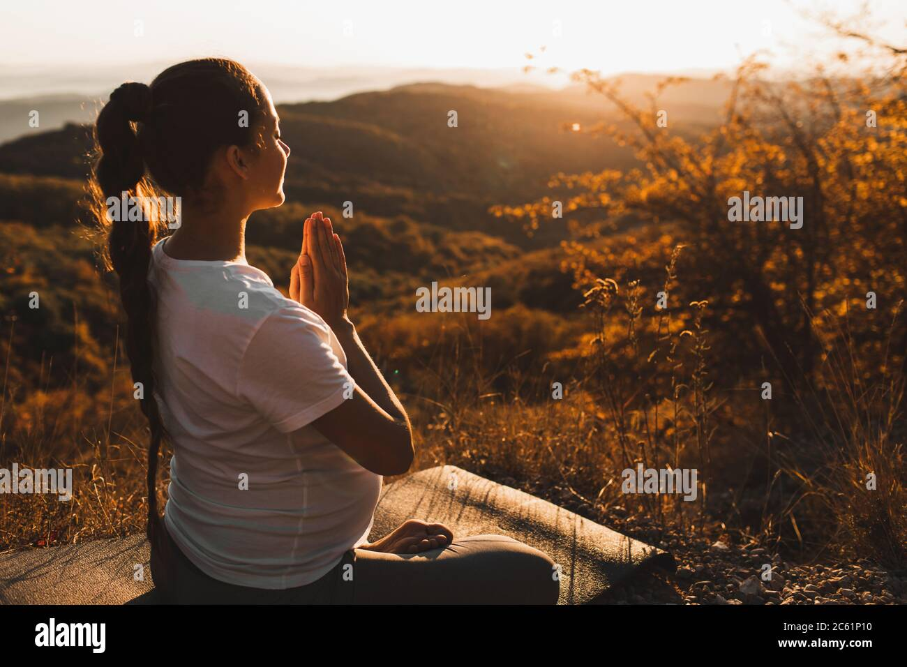 Spiritual and emotional concept of harmony with nature in maternity time. Pregnant woman praying alone outdoors on hill at sunset. Amazing autumn mountain view. Stock Photo