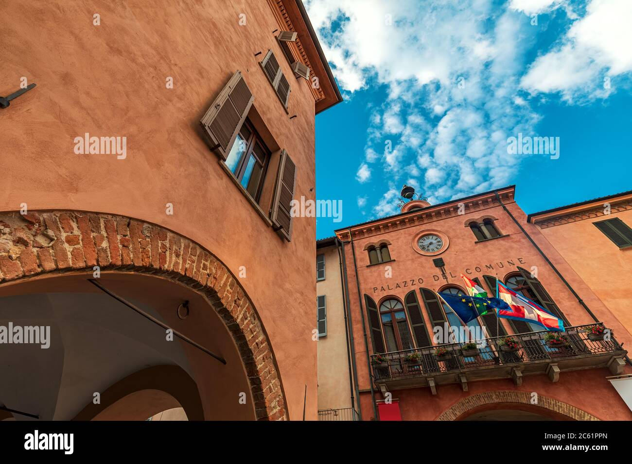 Old historic house and town hall with balcony, flags and clock under beautiful sky in Alba, Piedmont, Northern Italy (low angle view). Stock Photo