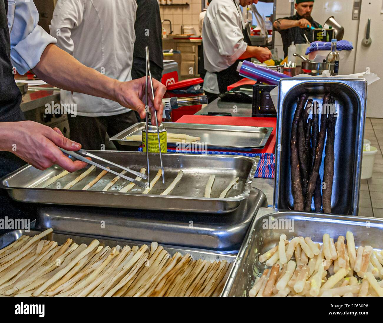 Black salsify preparation in the kitchen by Marco Müller. Three state forms promise variety with this often underestimated vegetable. Michelin Star Chef Marco Müller in Sankt Peter-Ording, Germany Stock Photo