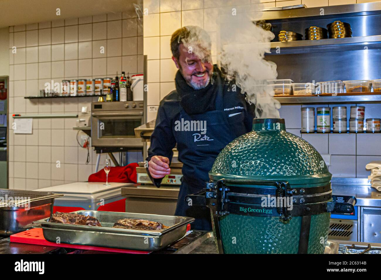 """German  3 Michelin star chef Marco Müller with Big Green Egg. One of the secrets of tender beef brisket is the """"reverse"""" order: first heat it in the oven at low heat and then grill it hot in its own smoke just before cutting it Stock Photo"""