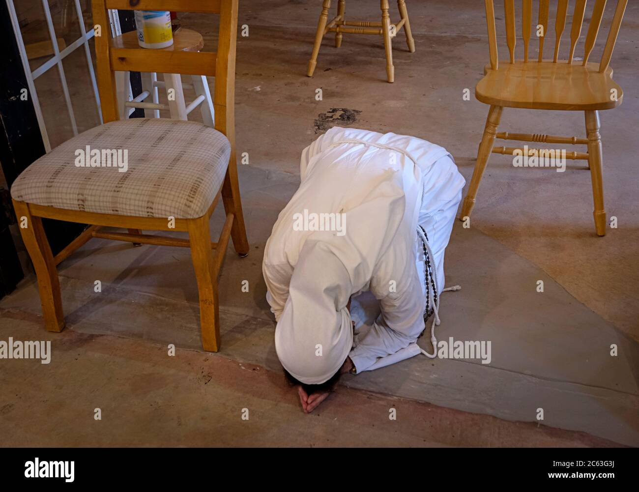 Catholic nun praying on the ground of a barn used as a chapel Stock Photo