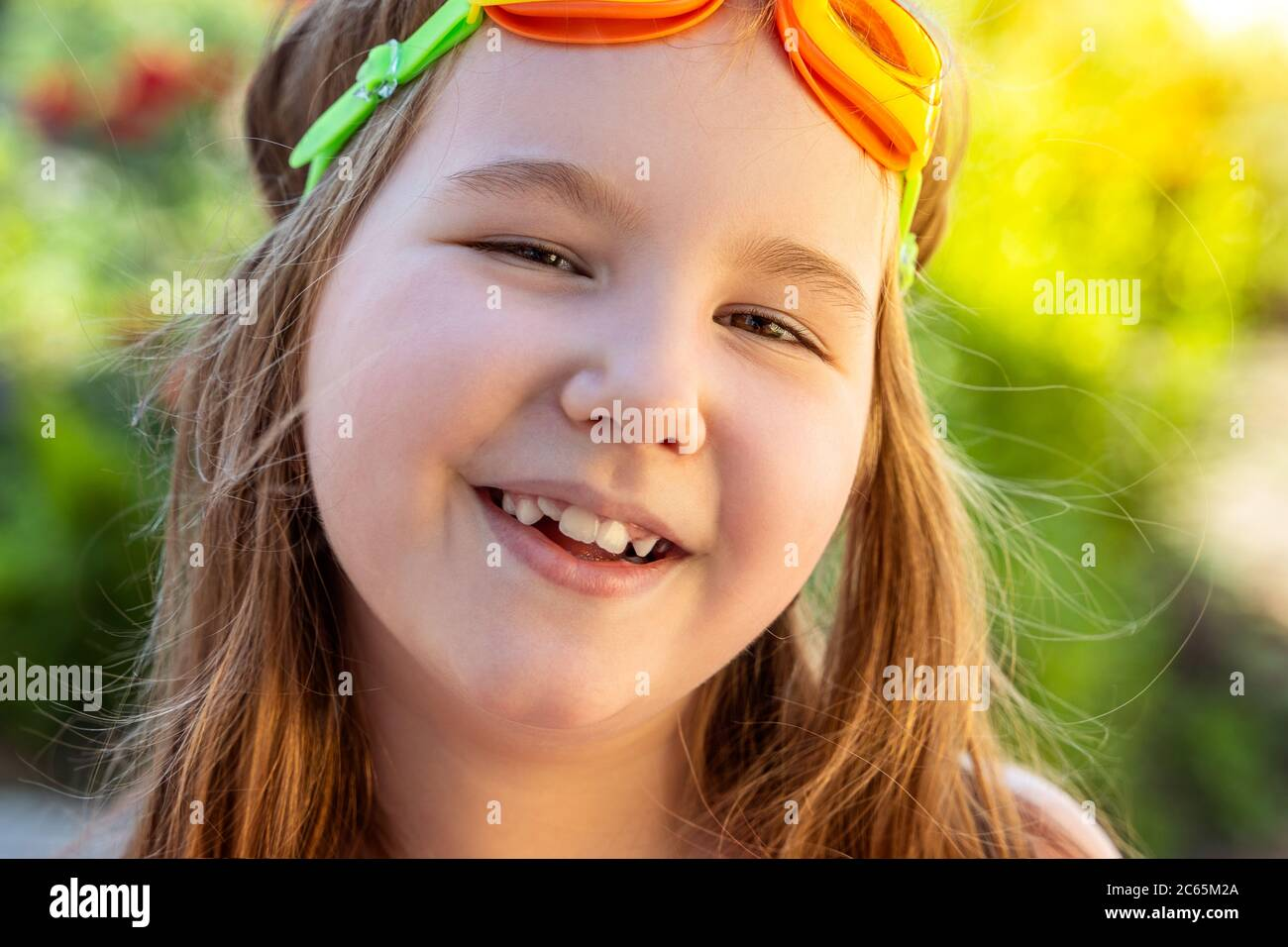Portrait of a beautiful smilling little girl with goggles for swimming pool. Activities with children outdoors. Summer having fun. Copy space. Stock Photo
