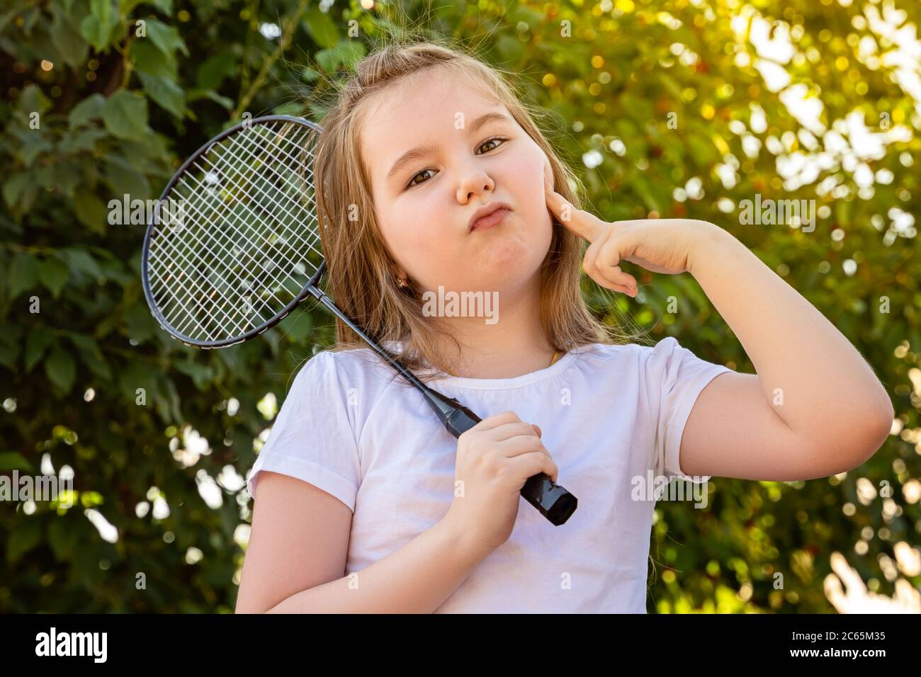 A little girl jokingly makes a glamorous face. Cute little girl playing badminton outdoors on warm and sunny summer day. Stock Photo