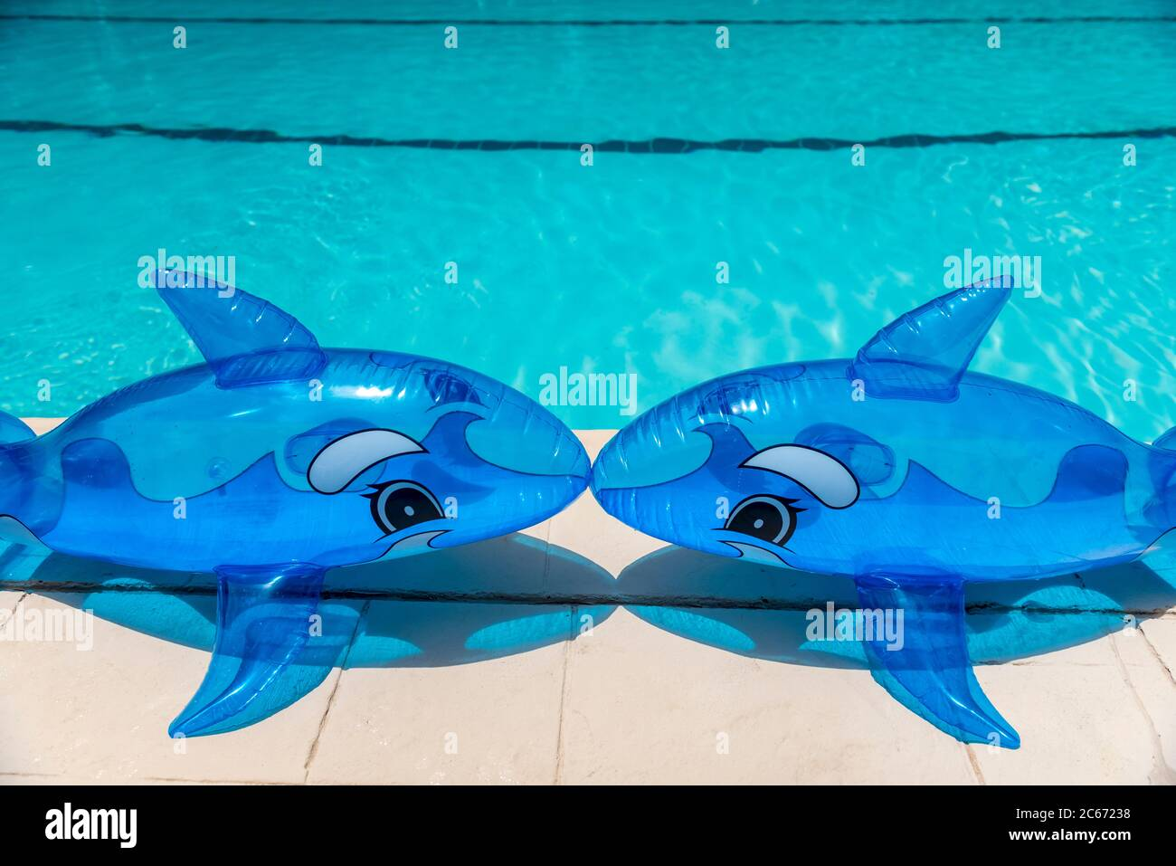 Inflatable pool toys on the deck of a poll with the water in the background. Stock Photo