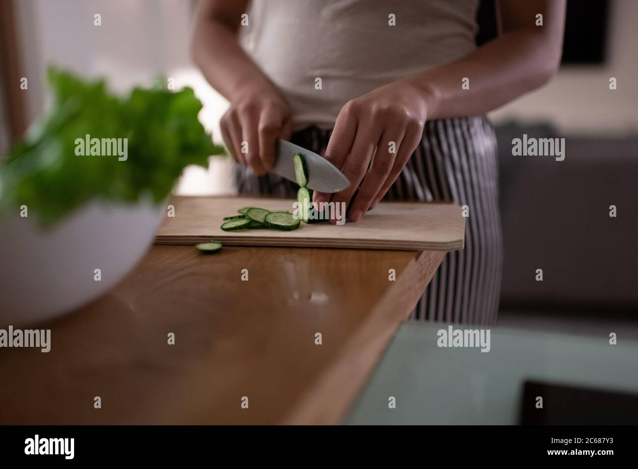 Cropped black lady chopping cucumber while cooking healthy dish for dinner at home Stock Photo