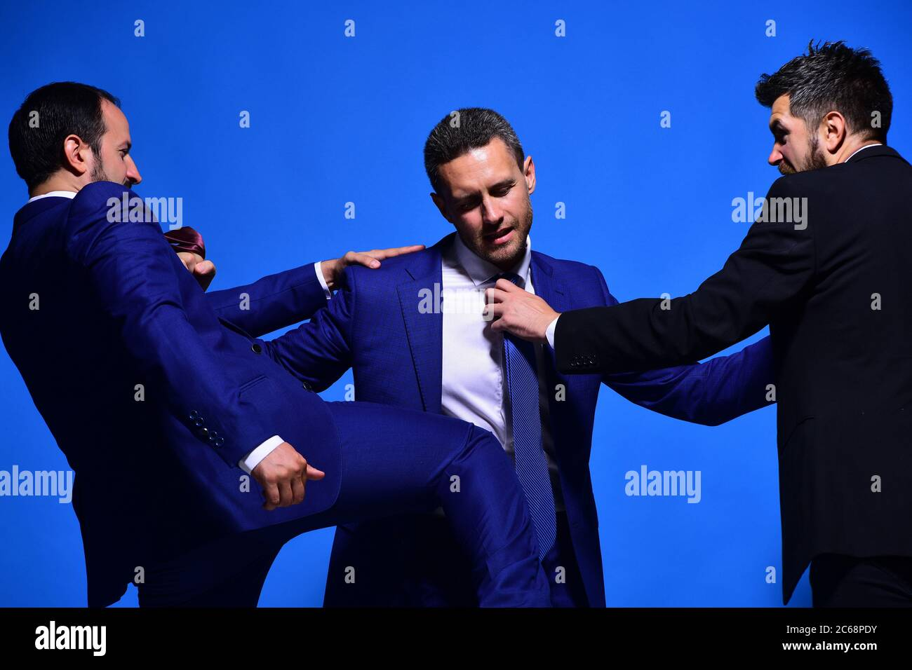 Business opposition and competition concept. Company leaders fight for business leadership. Businessmen with strict faces in formal wear on blue background. Coworkers decide upon best working position Stock Photo