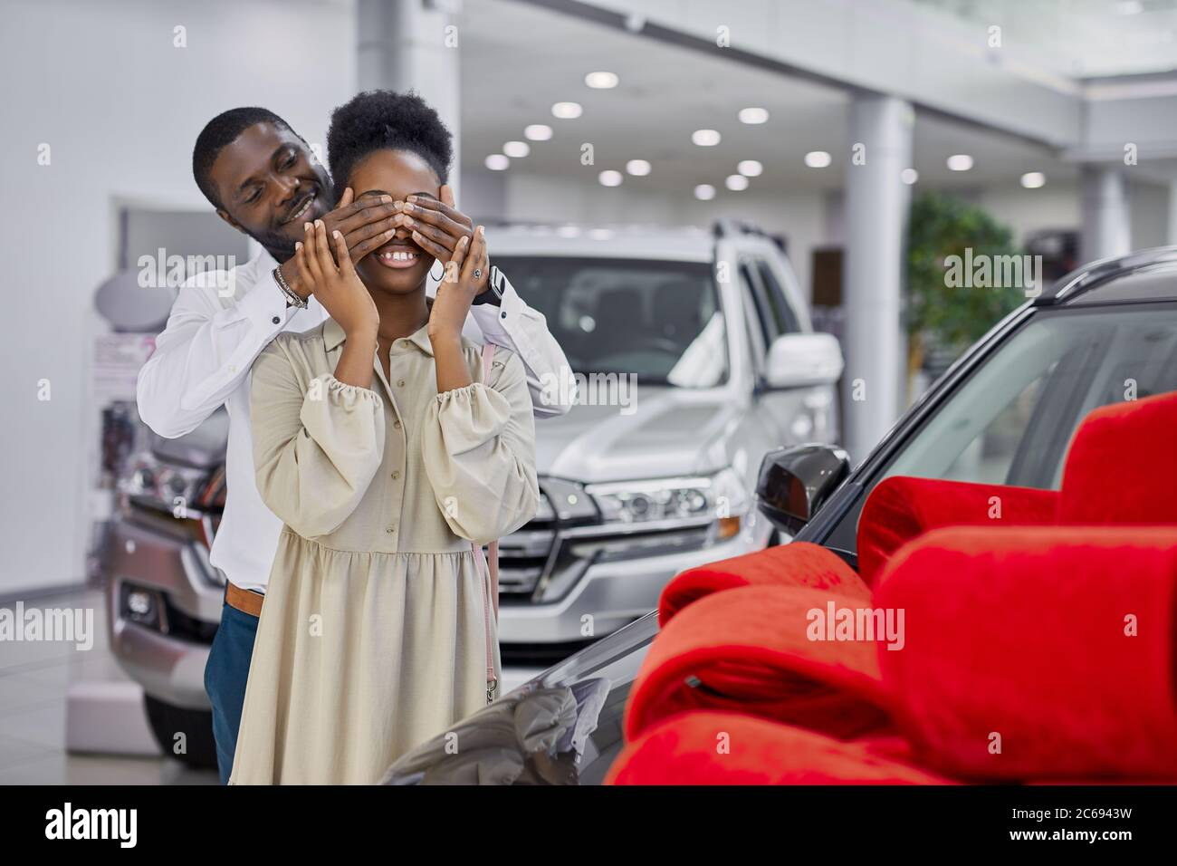 black man prepared gift to his wife, going to give new auto as a present, man closed woman's eyes during surprise. luxurious car is wrapped in red bow Stock Photo