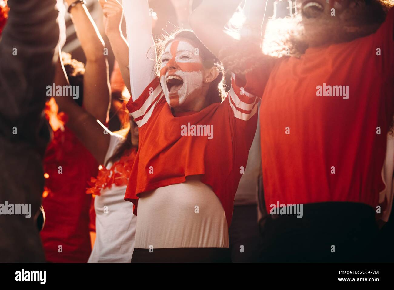 Excited England soccer fans celebrating in stands. English football supporters cheering over a goal in stadium. Stock Photo