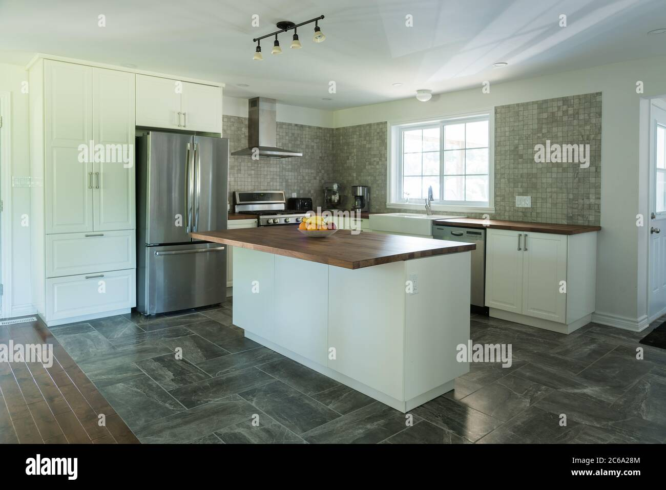 New Grey And White Kitchen With Marble Tiles Appliances And Timber Bench Tops Stock Photo Alamy