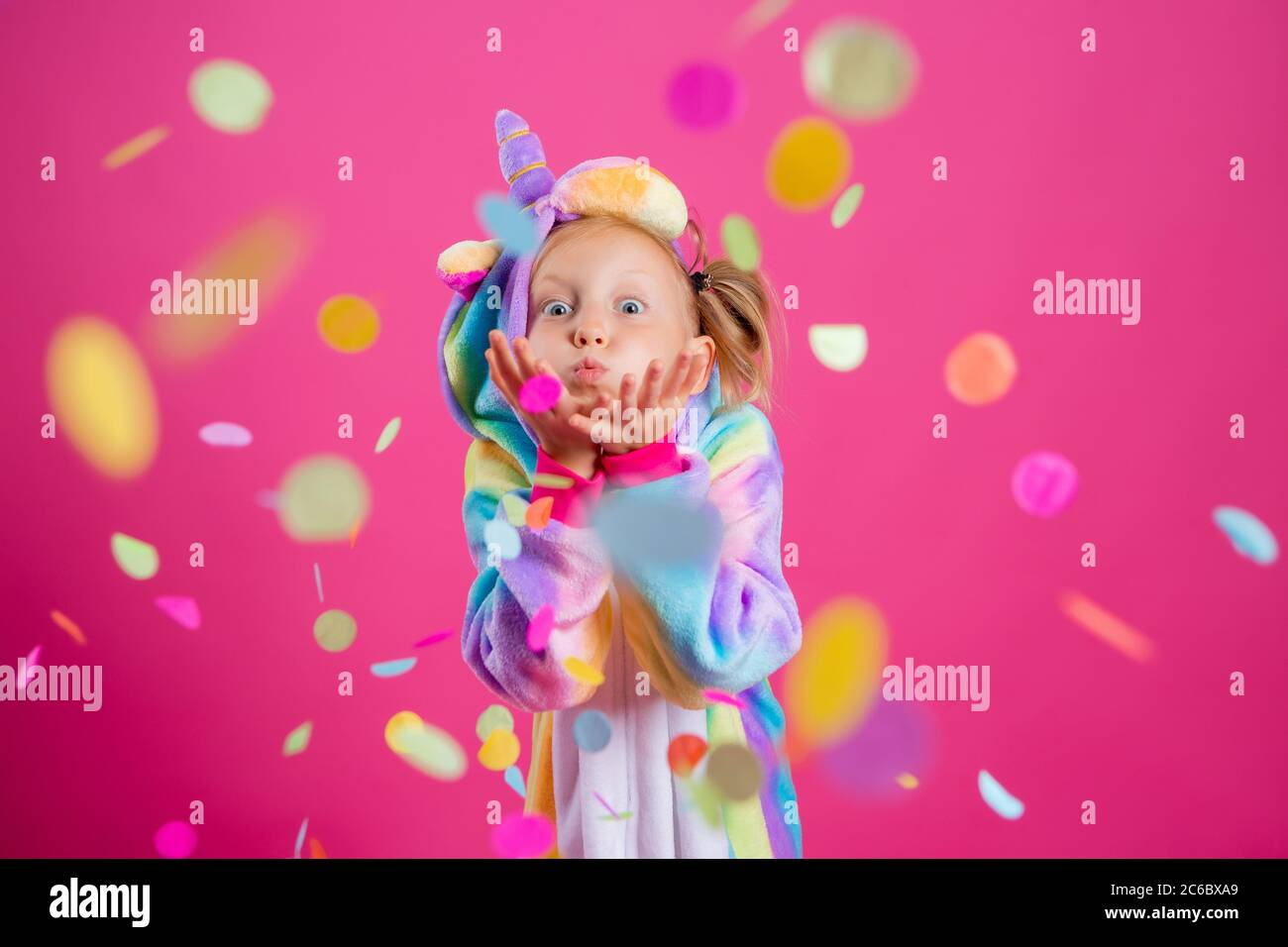 Happy little girl in kigurumi unicorn on a pink background rejoices in multi-colored confetti, space for text Stock Photo