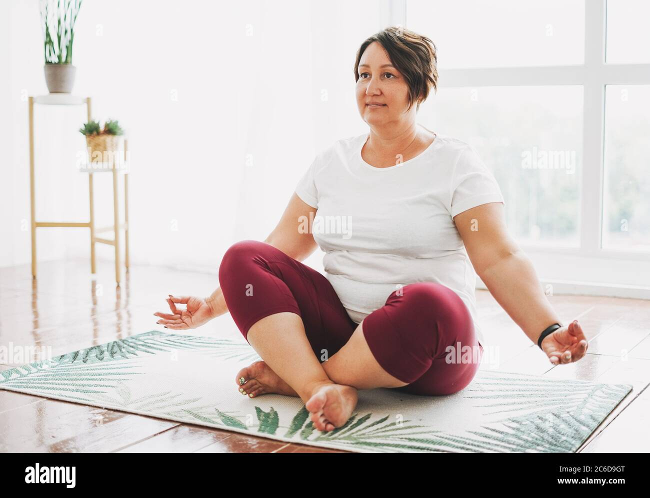 Adult charming brunette woman plus size body positive practice yoga at bright studio Stock Photo