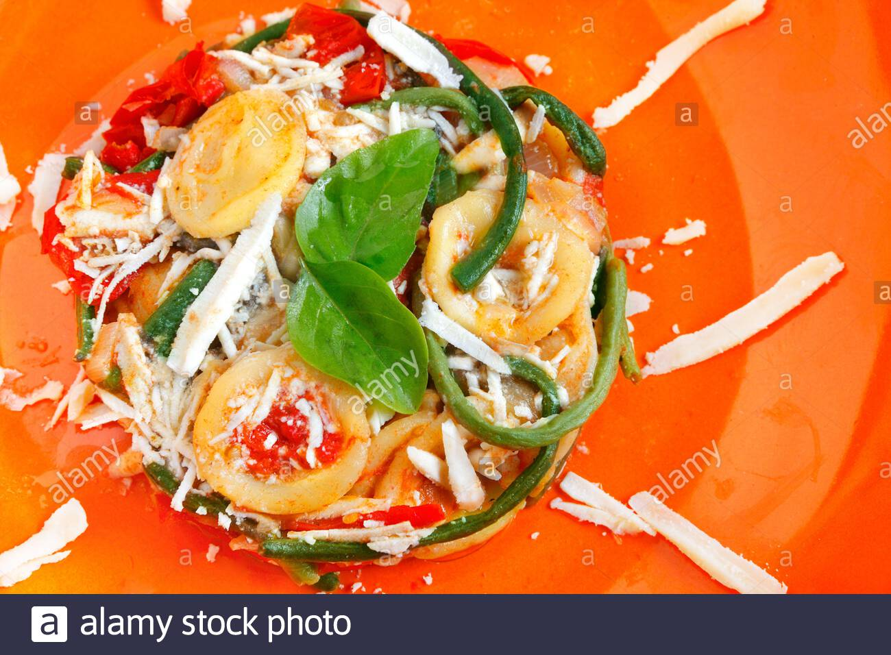 Traditional pasta orecchiette with tomatoes, green beans and cacioricotta cheese from Apulia, Italy Stock Photo