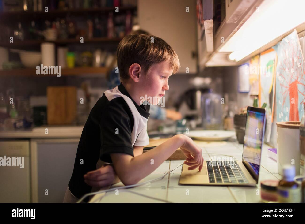 Boy doing homework at laptop on kitchen counter Stock Photo