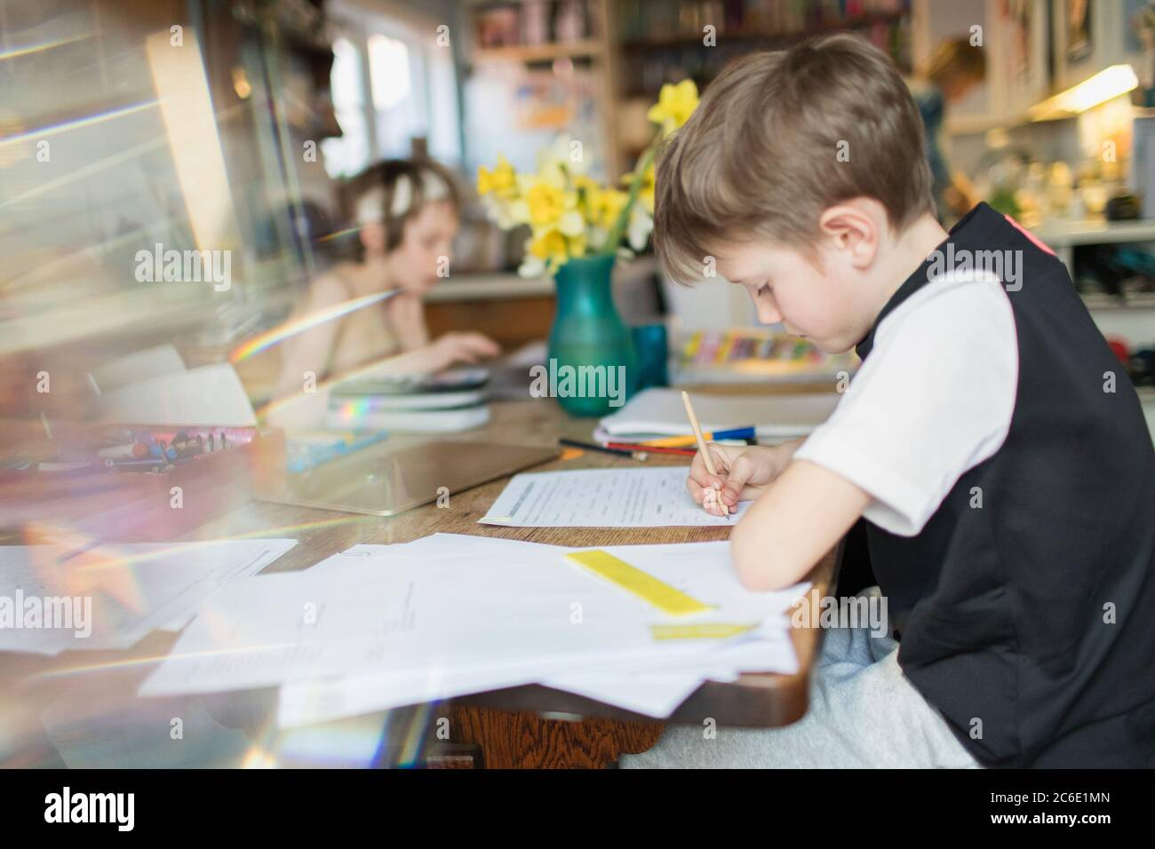 Boy doing homework at dining table Stock Photo